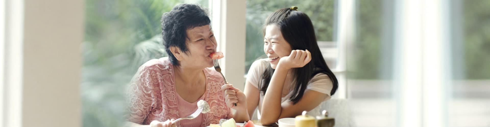 Asian adult daughter feeding fruit to senior mother