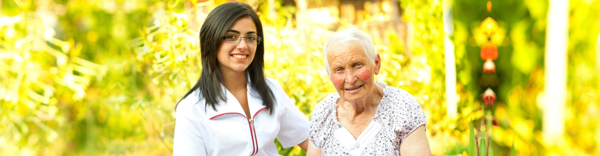 A young doctor / nurse visiting an elderly sick women holding her hands with caring attitude.