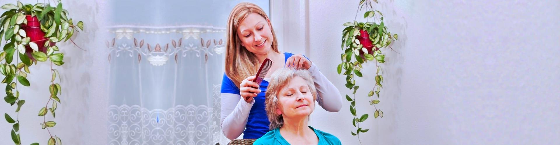 Blond young women combing seniors hair